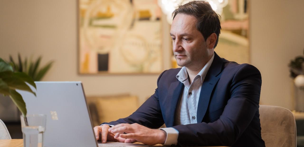 Bill Vasiliadis working on his laptop